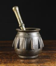 A 16th Century Spanish Bronze Apothecary Pestle & Mortar. The globular mortar decorated with protuberant fins below and ringed collar and flanged rim, 5½ ins (14 cms) high, 4½ ins (11.5 cms) in diameter. The pestle 9¾ ins (24.5 cms) in length.