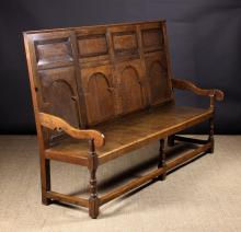 An 18th Century Joined Oak Settle.  The high back composed of four horizontal upper panels above arcaded base panels with silhouette cut scroll end arms on cannon barrel turned posts. The planked seat on three baluster turned front legs and square rear legs united by peripheral stretchers.