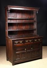A Fine 18th Century Joined Oak Canopy Dresser Circa 1720. The rack having a moulded hood with turned pendant finials either side overhanging plank-backed shelves. The base housing three fielded panel drawers above two panelled doors standing on square feet 76 ins (193 cms) high, 50 ins (128 cms) wide, 21½ ins (55 cms) deep.