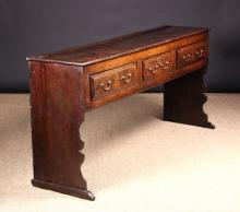 A Fine 18th Century Joined Oak Plank-End Low Dresser, Circa 1740. The frieze housing three fielded drawers fitted with brass swing handles and standing on silhouette cut ogee-front end boards  leading down to sledge feet. 33 ins (84 cms) high, 69 ins (175 cms) in length, 16½ ins (42 cms) deep.