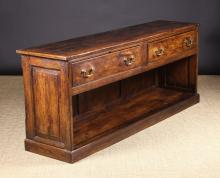 A Late Georgian Stained Pine Low Dresser/Counter.  The plank top having cleated ends above two frieze drawers retaining their original brass swan-neck handles. The boarded end supports leading down to a panel backed pot shelf below, 29½ ins (75 cms) high, 74 ins (188 cms) wide, 18½ ins (47 cms) deep.