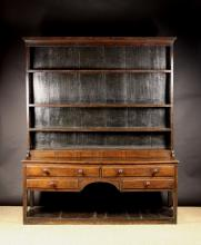 A Late Georgian Oak Country Dresser with Rack. The rack having four plank backed shelves above a boxed frieze inlaid with ebony banding. The base fitted with two frieze drawers above two side drawers flanking an arched kneehole, raised on square chamfered legs leading down to a pot shelf below. The drawers with lip moulded edges and turned wooden knob handles. 80½ ins (205 cms) high, 67 ins (170 cms) wide.
