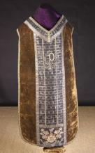 A Fine Brown Velvet Chasuble edged in silver metallic lace and centred with panels of black & silver embroidered brocade with an appliquéd crest dated 1663 to the back. The appliqué finely worked in coloured silks on a crimson velvet ground and embellished with tiny gold sequins.