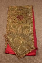 A Broad Metallic Gold Brocade Liturgical Stole backed in crimson silk with pockets stitched into the lining, 20½ ins x 101½ ins (52 cm x 258 cms).