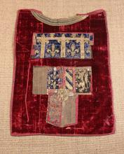 A 17th Century Crimson Velvet Tabard appliquéd with embroidered panels worked in metallic threads depicting fleur-de-lis and rampant lions.