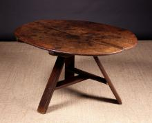 A Rare Late 16th/Early 17th Century Oak Tavern Table. The hinged oval twin plank top on a tripod base composed of splayed rails supports with moulded edges, united by a T-form planked stretcher, 25½ ins (65 cms) high, 47 ins x 35 ins (120 cms x 89 cms).