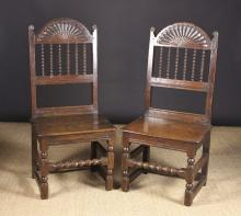 A Pair of Fine 17th Century Joined Oak Spindle Backed Chairs attributed to South Lancashire/North Cheshire. Each chair having an unusual dome topped cresting rail enriched with a fan of radial fluting above five bobbin turned spindles flanked by plain uprights with lobe cut finials. The planked seats on ball turned legs united by ball & reel turned front stretchers with plain stretchers to the sides and rear.