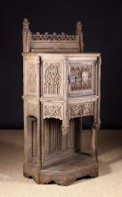 A 15th Century French Gothic Oak Dressoir intricately carved with elaborate tracery decoration. The canted cupboard surmounted by a pierced back rail flanked by crested finials with crocketed pinnacles. The central door fitted with a fine pierced iron lockplate and carved with a crowned shield emblazoned with three fleur-de-lys. The wrythen beaded pilasters adorned with small mythical beasts to the tops and pendant angels bearing shields to the base flanking a frieze drawer overhanging the canted pot shelf base and triple panelled back enriched with linen fold carving. 67 ins (170 cms) high, 33 ins (84 cms) wide, 21 ins (53 cms) deep.