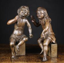 A Good Pair of Late 17th/Early 18th Century Carved Oak Curly-haired Putti holding sprigs of flowers and seated on later block stands, 21 ins (53 cms) high.