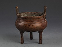 A TWO HANDLE BRONZE TRIPOD CENSER