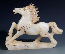 A FINELY CARVED HORSE SHAPED WHITE JADE