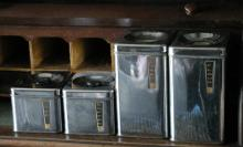 set of 4 Art Deco period chrome kitchen canisters with brass plaques
