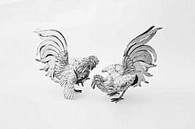 A pair of silver table decorations in the form of a rooster 20th century Both with spread wings, one with raised right foot.Third grade silver, approx. weight 1216 grams.H. 22.5 / 25 cm(2x)
