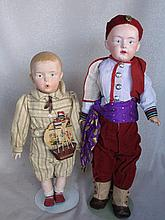 Two reproduction Gebruder Heubach earthenware dolls. Whistler 36cm with toy