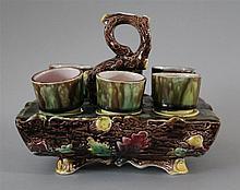 Majolica Egg Cup Set. Six egg cups in bark and leaf patterned holder. Holder measures 6