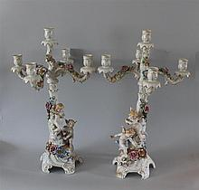 Pair of German Porcelain Figural Candelabras. Candlesticks with Putti in flight, adorned with applied porcelain flowers supporting a...