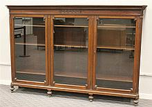 Bookcase, Mahogany, Molded Cornice, Seascroll Carved Top, Three Glazed Doors with Wood Shelving on Turned Feet, (Damage to Right Foo...