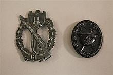 Lot of two German WW II medals. Included is a stamped silvered infantry assault badge displaying a grey metal finish devoid of its s...