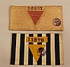 German WW II concentration armbands (2). One armband made of thin cotton striped material displays a yellow triangle below an ink st...