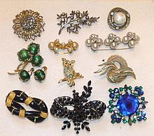 Eleven vintage costume brooches, one with matching