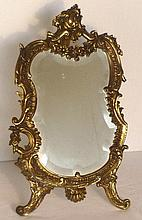 Gilt metal table mirror of easel form with scroll