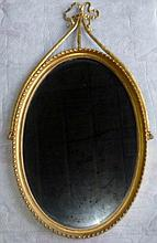 Oval gilt gesso wall mirror, the top adorned with