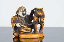 Carved Japanese Netsuke figure of a man and monkey with a drum.