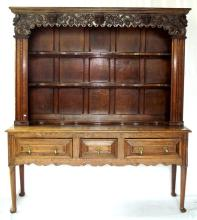 Georgian 3 Drawer Dresser Base with later Victorian Carved Plate Rack. 18th/19th c. The well carved cornice over 3 shaped shelves and the multiple panel back compliments the 3 drawer base with drop handles and shaped frieze on turned legs with pad feet.  Height  75 in.  Width 68 in.  Depth 20 in.
