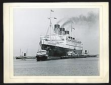 R.M.S. Queen Mary with tugs.