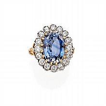 BAGUE en or jaune et or gris sertie d'un saphir ovale dans un entourage de diamants taillés en brillant. Poids de la pierre env....