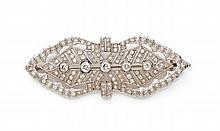 BROCHE en platine faite d'un losange ajouré et agrafé de bandeaux sertis de diamants taillés en brillant. Epoque 1930 Long. :...