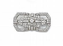 BROCHE RECTANGULAIRE A PANS en platine et or gris ajourée et sertie de diamants taillés en brillant et en baguette, au centre l'un...