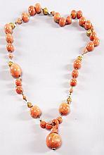 ANONYME, Très joli collier composé de boules de corail intercalées de petites boules dorées et boules de corail sculptées. Poids bru...