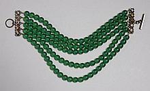 Jean Paul GAULTIER, Tour de cou composé de cinq rang de perles en pâte de verre verte, le fermoir figurant des fleurs stylisées. Lon...