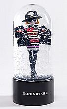 Sonia RYKIEL, Grande boule de neige musicale à l'effigie de la créatrice de la maison chargée de paquets. Haut. 22,5 cm. Parfait éta..