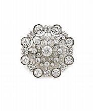 BROCHE En platine (950), stylisée d'une rosace finement ajourée, ornée en serti perlé de diamants demi-taille, celui du centre plu...
