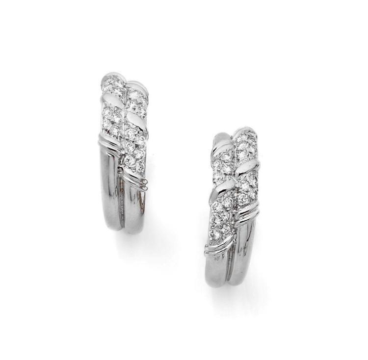 PAIRE DE CREOLES  en or gris formées chacune d'un double demi-jonc coupé de quatre segments sertis de brillants. Diam : 2.8 cm -...
