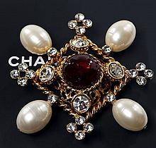 CHANEL, 2003, Magnifique broche losangique en métal doré ajouré ornée en son centre d'un cabochon de verre rouge. Pavage de strass r..
