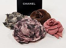 CHANEL, Quatre broches camélia,  - deux en mousseline de soie, signées sur plaque, l'une dans les tons rose et noir, l'autre dans...