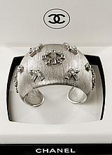CHANEL Automne 2006, Bracelet manchette en acier brossé et motifs rayonnants de strass, siglé. Signé sur plaque. Très bon état. Pass...