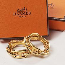HERMES Paris, Deux anneaux de foulards en métal doré et formant chaîne d'ancre. Two scarf rings in golden metal.