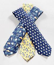 HERMES Paris, Trois cravates en soie. L'une bleue à décor de poussins, la deuxième jaune à décor de poupées russes (tâchée), la dern..