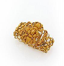 BRACELET en or jaune entièrement orné d'un motif ciselé au repoussé de rinceaux et feuilles, le tour de poignet de type résille.R...