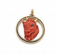 PENDENTIF en or jaune ornée d'une tête de taureau sculptée en corail, les yeux sertis d'émeraudes, les cornes et la monture en or...