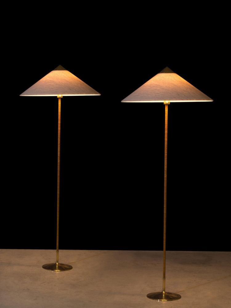 Paavo TYNELL (1890-1973) Paire de lampadaires mod. 9602 - Circa 1950 Base en laiton, fût recouvert de rotin, abat-jour en tissu et l...
