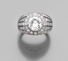 BOUCHERON BAGUE DE GENRE CHEVALIERE En platine (950), ornée en serti clos d'un diamant demi-taille dans un entourage et un épaul...