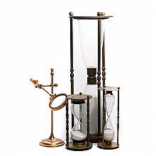 Three Hourglasses and a Brass Magnifying Glass on Stand