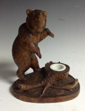 A Black Forest novelty inkwell, carved with a bear, on hind legs, traversin