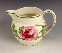 A Wedgwood Pink Rose creamware jug, painted by F. H. Cox with bold roses an