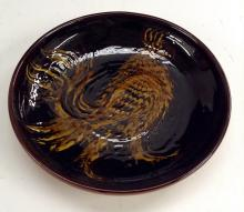 A Hawkshead terracotta slipware plate, applied with a grotesque bird, 25cm